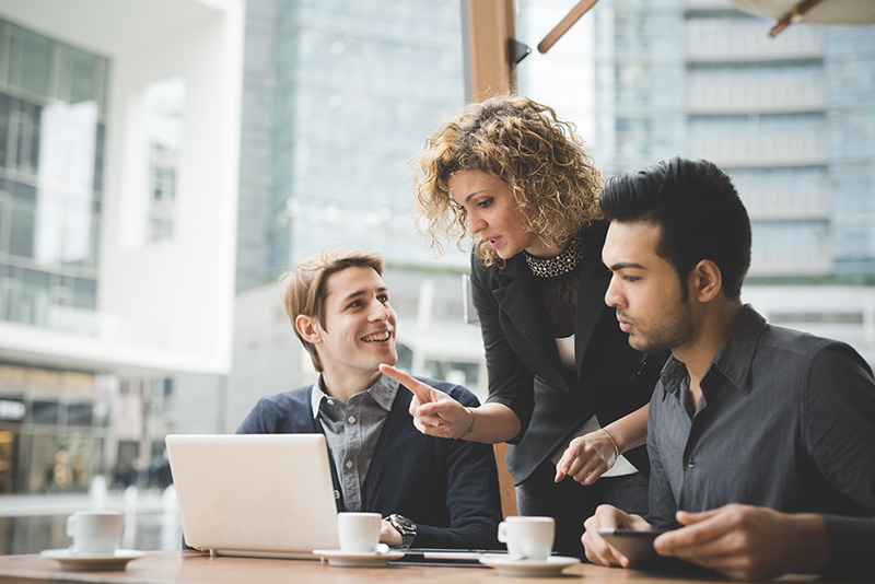 three people talking at a desk around a laptop